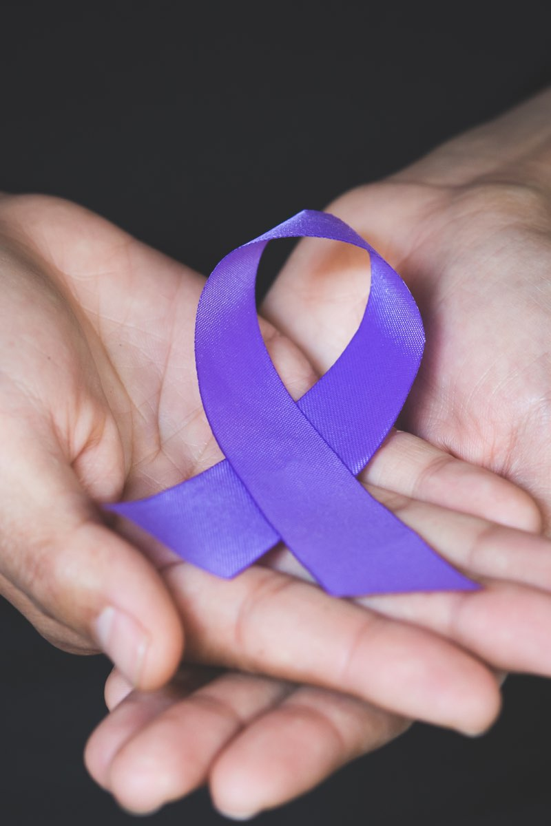 Two hands holding Domestic Violence Awareness Month purple ribbon