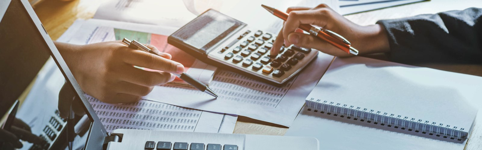 Accountants adding up figures with a calculator on desk