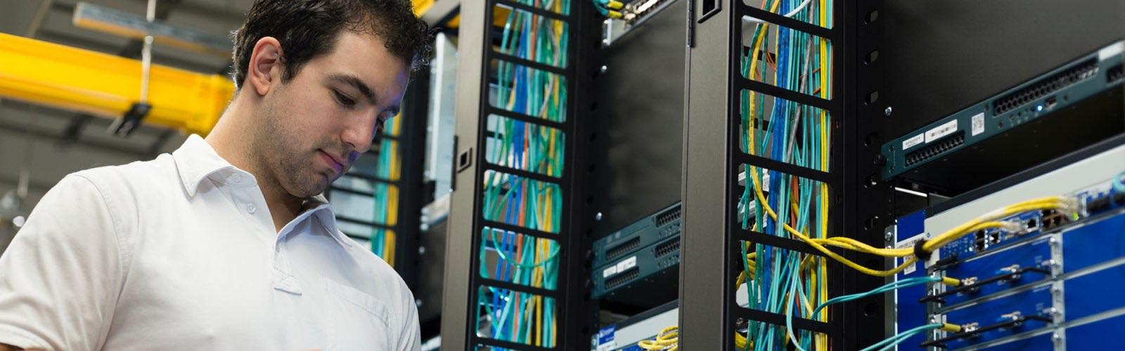 Information technology professional looking at tablet in front of server rack
