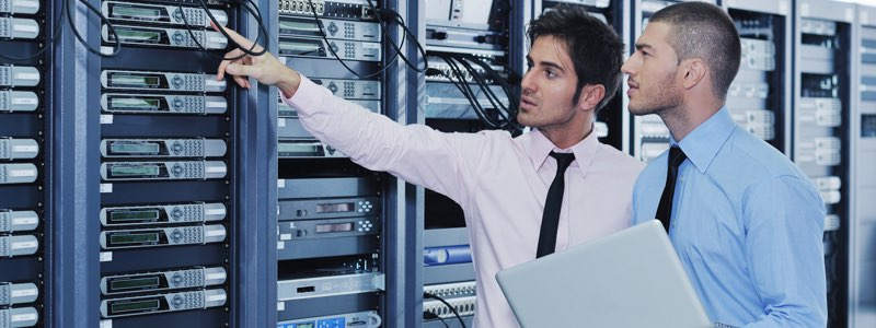 Information technology professionals inspecting server racks