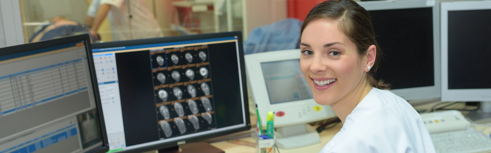 Female nurse in front of computer screen smiling