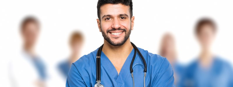 Male nurse smiling in front of team of doctors