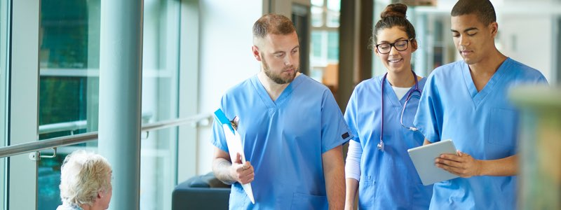 3 nurses walking through hospital talking