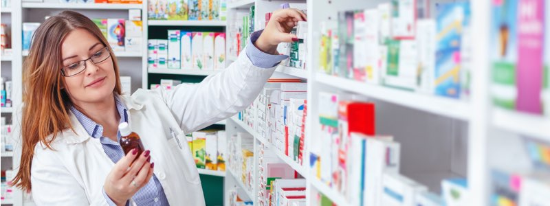 Female pharmacist filling prescription from shelf of pharmacy