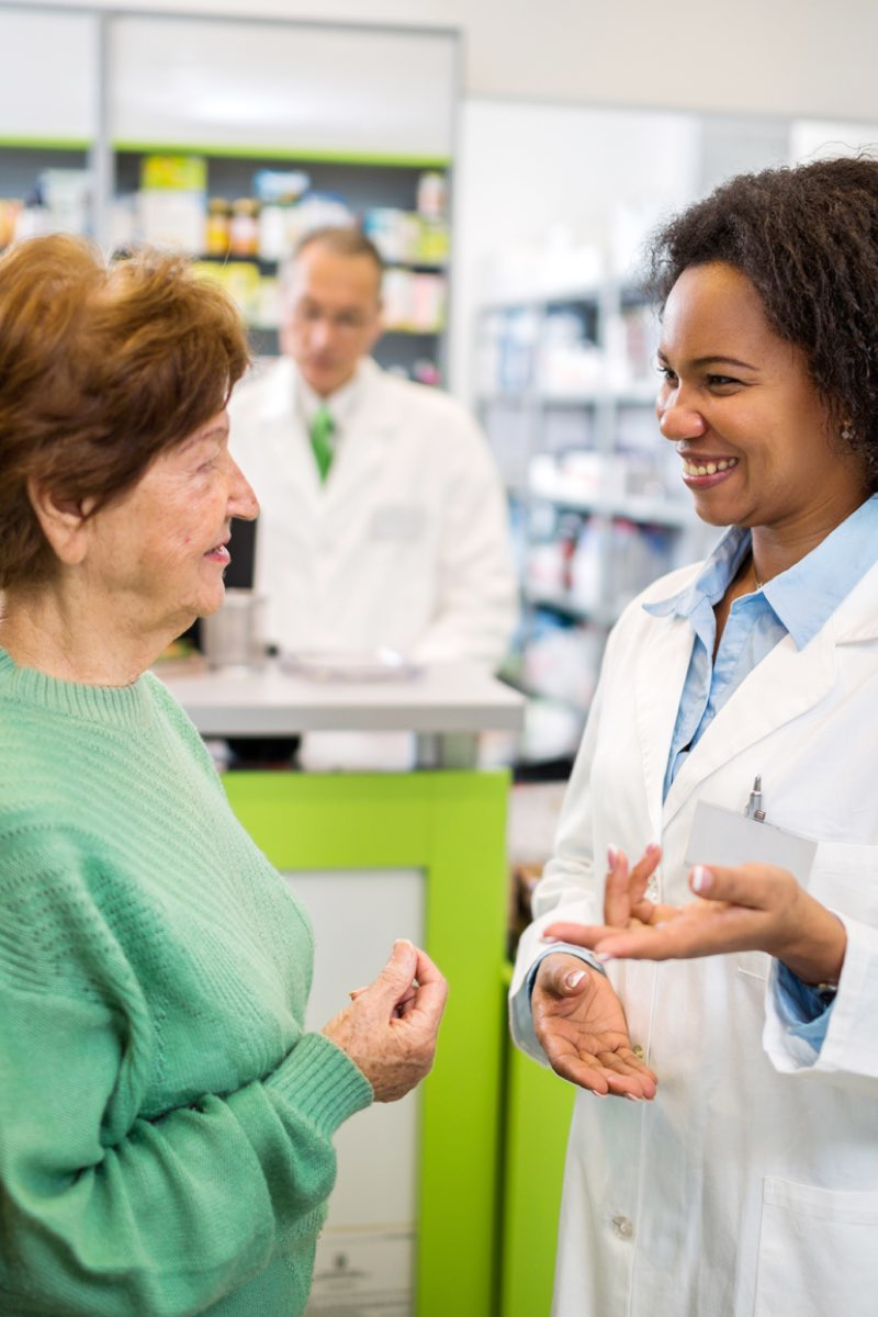 Female pharmacist speaking with patients in pharmacy
