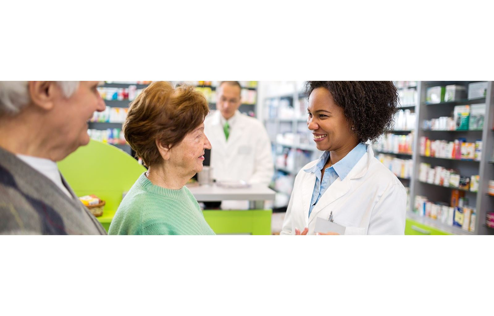 Woman pharmacist in pharmacy consulting elderly patients