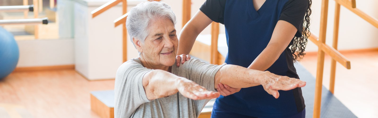 Physical therapist holding older patient's arms outstretched