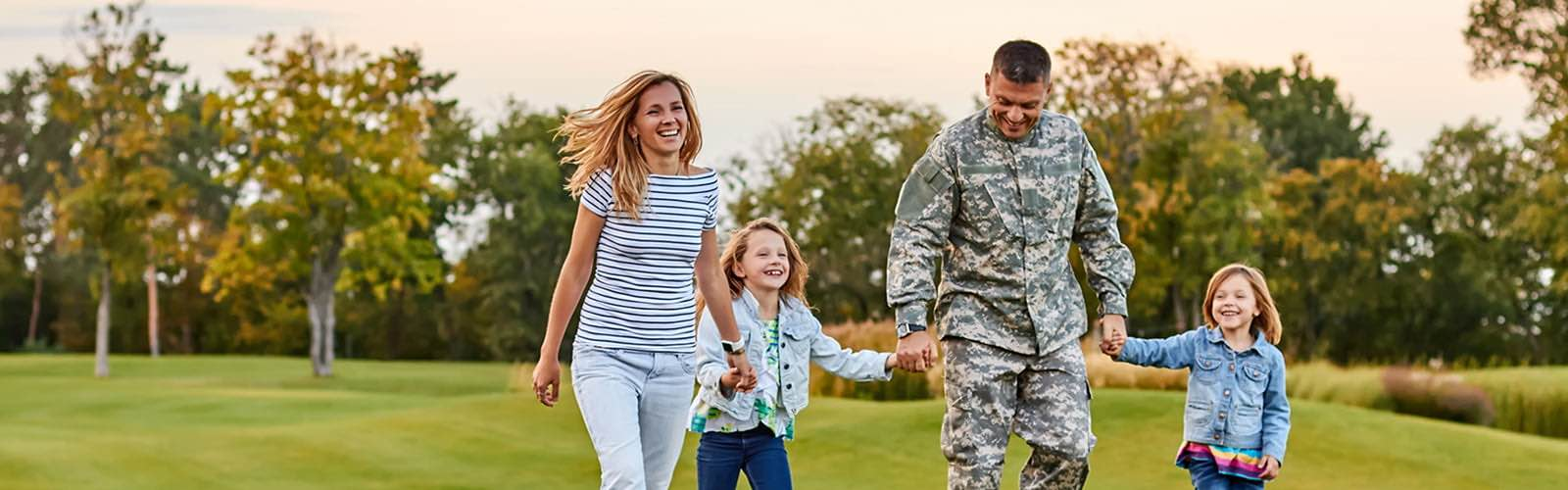 Military serviceman with family in park