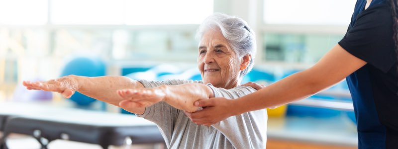 Occupational therapist holding older patient's arms outstretched
