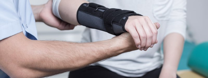 Occupational therapist holding patient's arm in cast