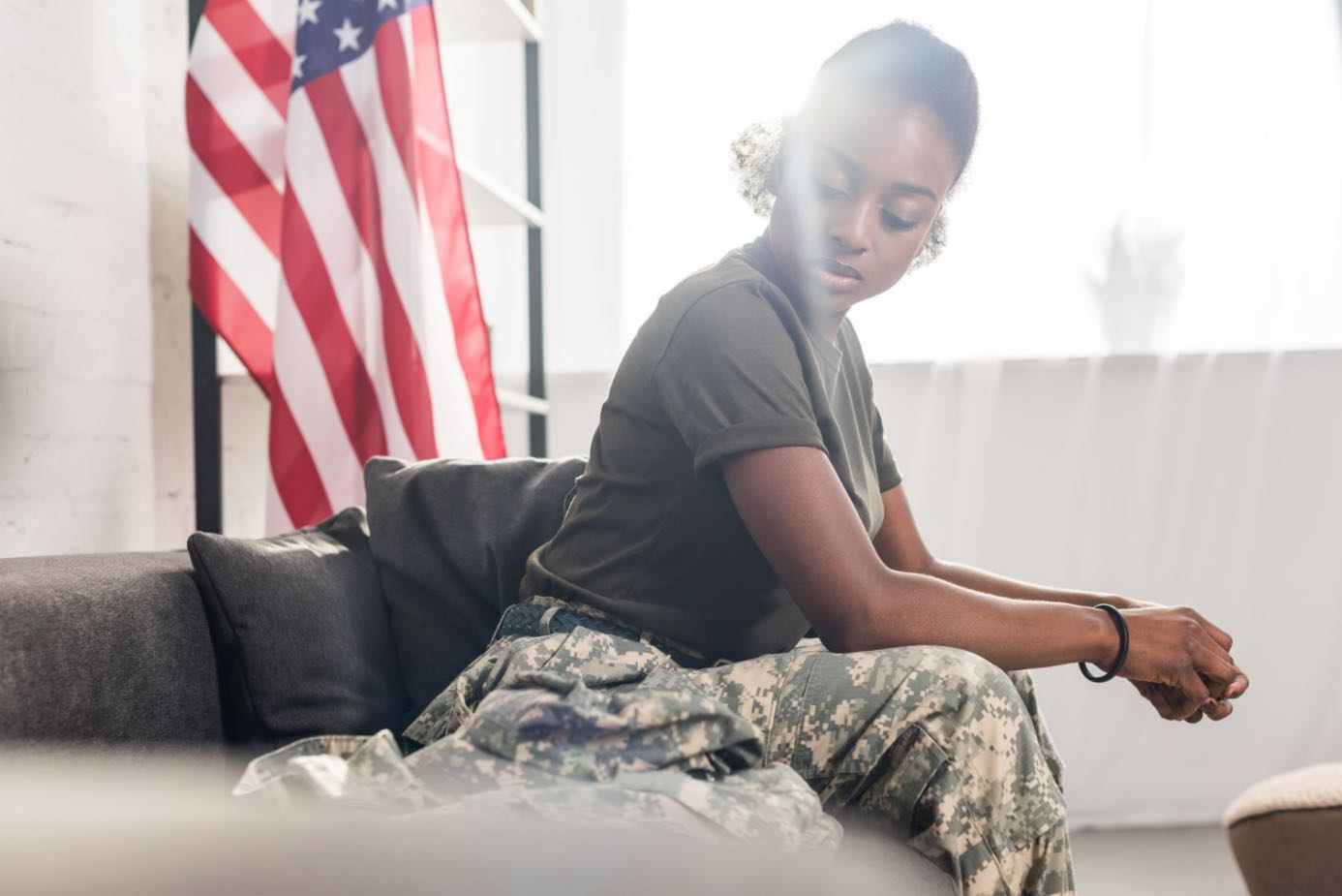 Female soldier sitting in front of American flag